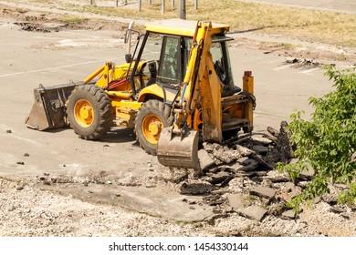 Yellow Excavator Dig the Asphalt with Tractor Bucket. Bulldozer Dismantles Asphalt at Work