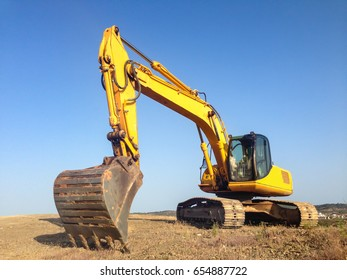 yellow excavator, digger parked on dusty ground on a summer day with blue sky