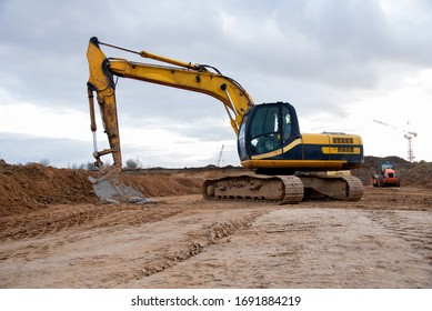 Yellow excavator during earthworks at construction site. Backhoe digging the ground for the foundation and for laying sewer pipes district heating. Earth-moving heavy equipment