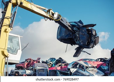 Yellow excavator loads car in the scrap yard