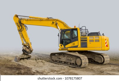yellow excavator at a loamy construction site, partly isolated in grey back