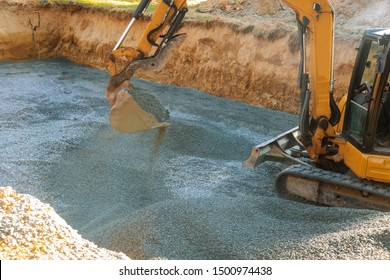 A yellow excavator moving gravel in the foundation in the house poles on gravel