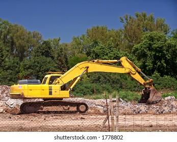 Yellow excavator on construcion site.