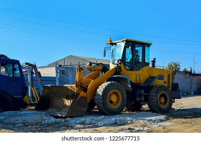 Yellow excavator on the construction site is preparing to load the soil into the dump truck. Wheel loader with iron bucket