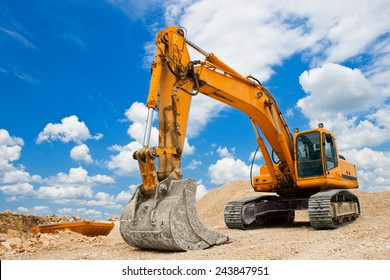 Yellow excavator on a construction site against blue sky