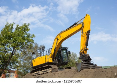 yellow excavator on the soil pile against blue sky