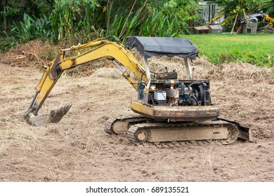Yellow excavator parked.Old small excavator parked outdoor