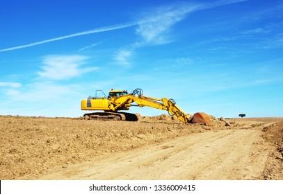 yellow excavator in plowed field