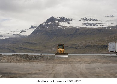 Yellow excavator with a snowy mountain background. Island