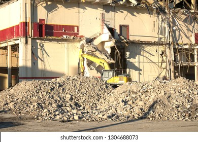 Yellow excavator working on a pile of rubble