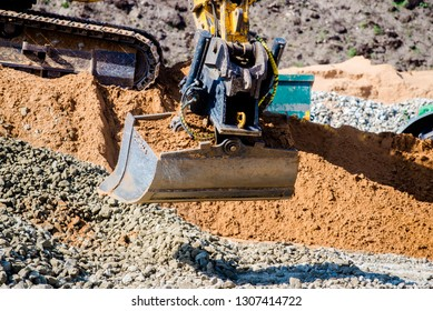 Yellow excavator working on sand dunes. Scoop close-up