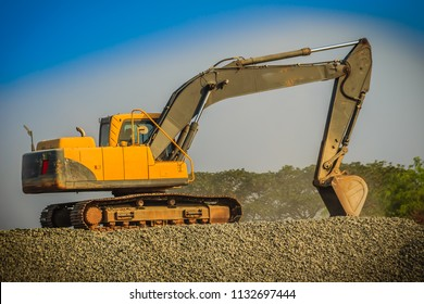 Yellow excavator is working in quarry against the background of crushed stone storage.