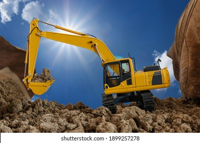 Yellow excavators are digging the soil in the construction site with the sky and sunbeam background