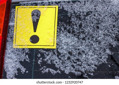 The yellow exclamation mark on the back window of the car covered by snow.