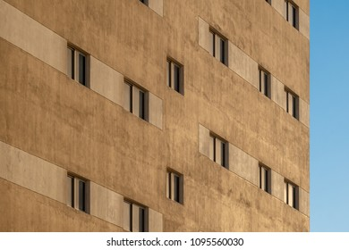 The yellow facade of an apartment block with reflective windows at sunset against a blue sky.