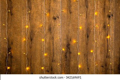 Yellow fairy lights on a wooden wall - holyday background.