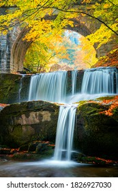 Yellow Fall Autumn landscape - river waterfall in colorful autumn forest park with yellow red leaves with old bridge, focus on foreground