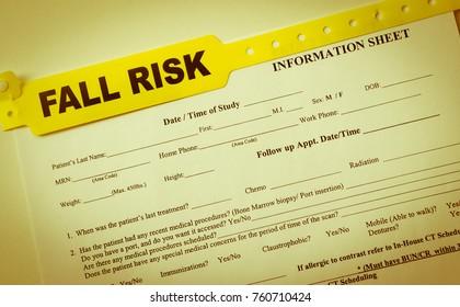 Yellow fall risk bracelet over top hospital paperwork