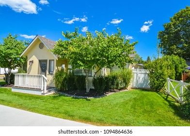 Yellow family house with small front yard. Family house with concrete pathway in front of the entrance on sunny day
