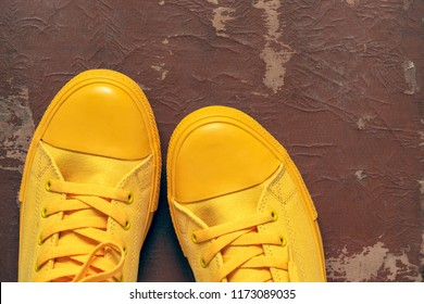 yellow fashionable gym shoes or sports boots closeup against the background of old brown skin