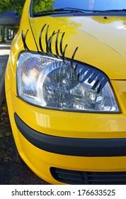 """Yellow """"female"""" car with seductive eyelash."""