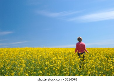 Yellow field, the blue sky and the woman in pink
