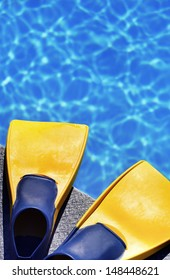 yellow fins on feet at edge of blue swimming pool