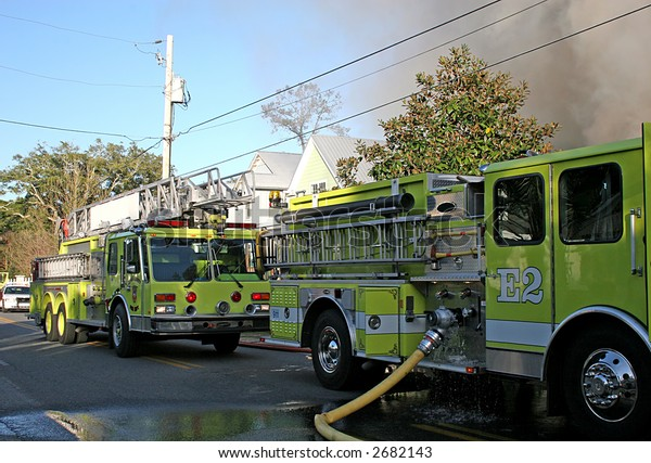 Yellow fire trucks at the scene of a house fire