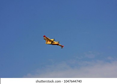 Yellow firefighter plane flying under blue sky