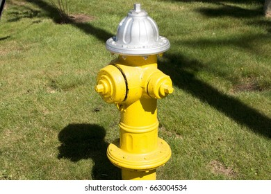 A yellow firehydrant in a local neighborhood