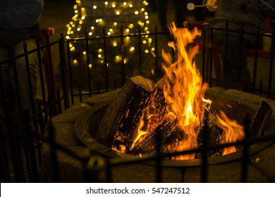 yellow Firewood fire in a brick fire pit dark background with little Christmas light on tree truck