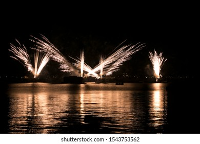 Yellow fireworks reflections in water