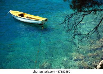 Yellow fishing boat on the emerald sea