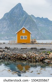 A yellow fishing cabin in Sakrisøy, a small fishing village in Moskenes Municipality on Lofoten islands in Nordland county, Norway with a mountain in background