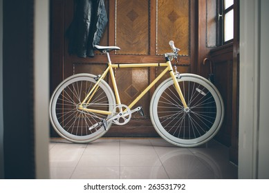A yellow fixed-gear bicycle (also called fixie) with a white chain at home