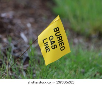 Yellow flag with a green grass background marks the location of a buried gas line to prevent accidental rupture during excavation