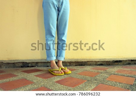 900e381d6d02 Yellow Flip Flops. Female Wearing Sandals and Blue Jeans Standing on Tile  Floor Background Great