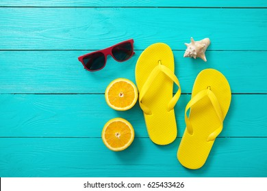 Yellow flip flops, red sunglasses, shell and orange fruit on blue wooden background. Top view and summer time, picturesque
