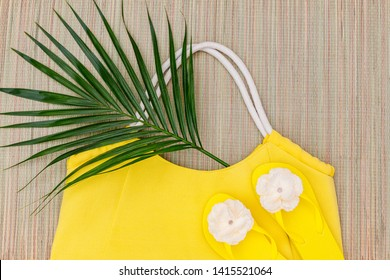 Yellow flipflops shoes and bag on  straw beach Mat background, top view, with copy space. Toe sandals, flat lay, text place. Summer concept with palm leaf