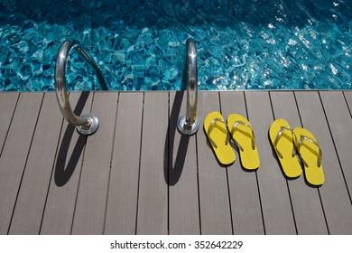 6ca6a98df1f74f Yellow flips flops beside swimming pool