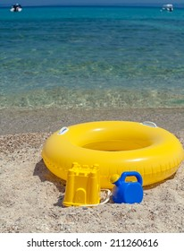 Yellow float and child beach toys lying on beach over blue sea. Summer vacation concept.