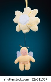 A yellow flower and bumblebee baby mobile on a blue background with a natural black vignette.