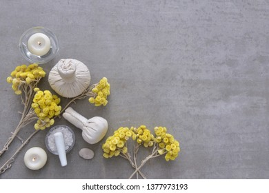 Yellow flower and candle and herbal ball ,stone,salt in bowl  candle on gray background