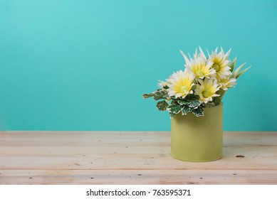 yellow flower on wooden table with green background