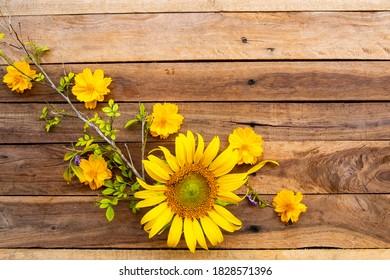 Gelbe Blumen, Kosmos, Ringelblumen und Sonnenblumen Arrangement auf Holzhintergrund