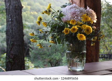 Yellow flowers in glass jar