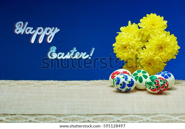 "Yellow flowers and painted in hand-made Easter eggs on a blue background with the inscription ""Happy Easter"""