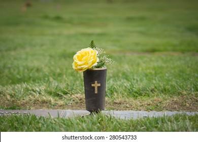 Yellow flowers set at graveside in memorial cemetery in California.