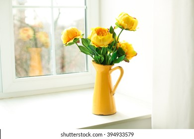yellow flowers in a yellow vase on a windowsill