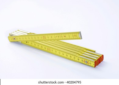 A yellow folding measuring stick is spread out on white background